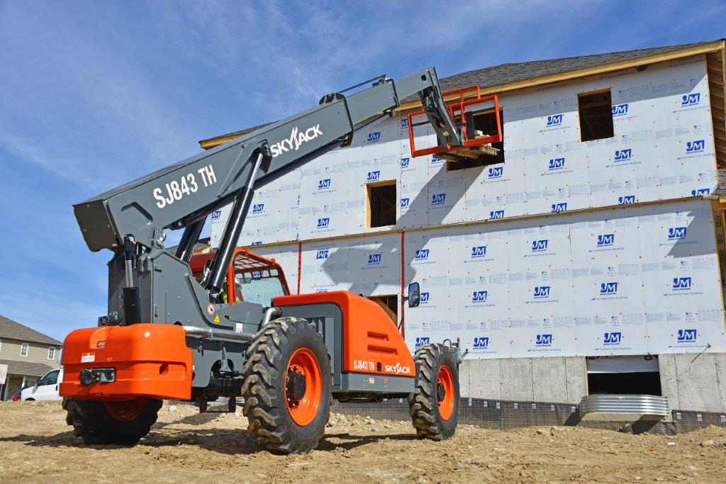 SkyJack SJ843 TH lifting wood into a house that is being constructed.
